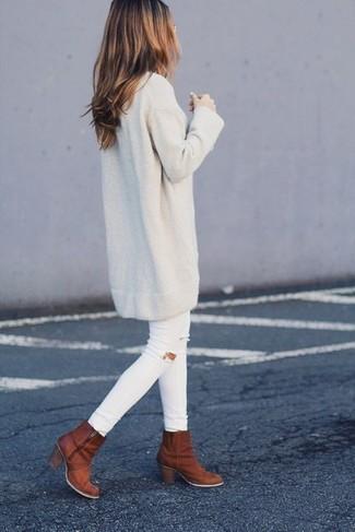 Как и с чем носить: бежевое платье-свитер, белые рваные джинсы скинни, табачные кожаные ботильоны