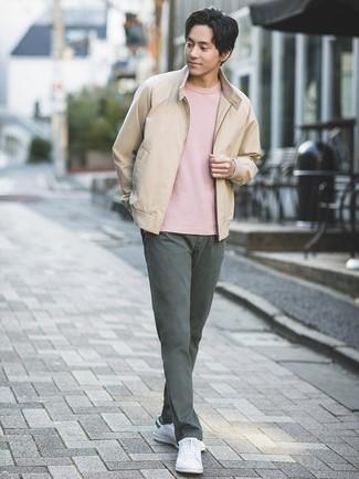 Как и с чем носить: бежевый бомбер, розовая футболка с круглым вырезом, темно-серые брюки чинос, белые кожаные низкие кеды