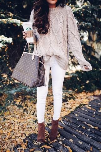 Как и с чем носить: бежевый вязаный свитер, белые джинсы скинни, коричневые замшевые ботильоны, темно-коричневая кожаная большая сумка с принтом