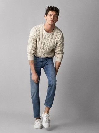 Модные мужские луки 2020 фото: Сочетание бежевого вязаного свитера и синих джинсов поможет подчеркнуть твой индивидуальный стиль и выигрышно выделиться из толпы. Белые низкие кеды из плотной ткани — беспроигрышный выбор, чтобы закончить ансамбль.