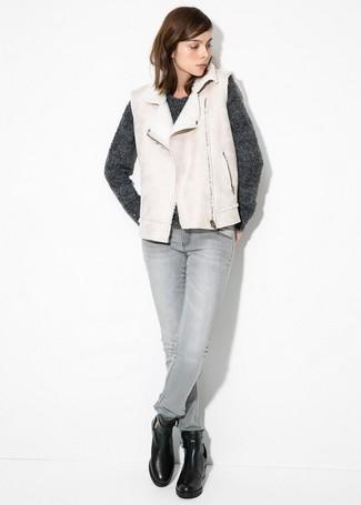 Как и с чем носить: бежевый жилет из овчины, темно-серый свитер с круглым вырезом, серые джинсы скинни, черные кожаные ботильоны