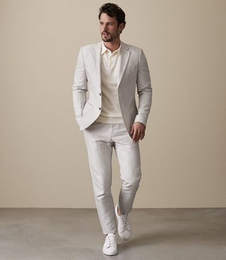 Как и с чем носить: бежевый костюм, бежевая футболка-поло, белые кожаные низкие кеды