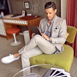 Комбо из бежевого костюма и серой рубашки с длинным рукавом с принтом — олицетворение строгого делового стиля. Почему бы не добавить в этот лук толику легкой небрежности с помощью белых низких кед?