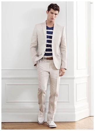 Как и с чем носить: бежевый костюм, темно-сине-белая футболка с круглым вырезом в горизонтальную полоску, белые низкие кеды, бело-черный ремень из плотной ткани в горизонтальную полоску