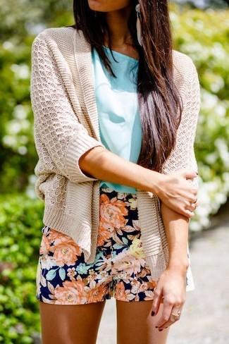 Как и с чем носить: бежевый вязаный открытый кардиган, бирюзовая блуза с коротким рукавом, темно-синие шорты с цветочным принтом, бежевые серьги