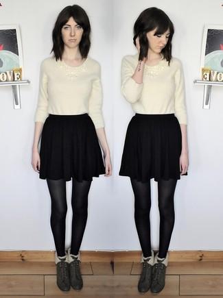 Как и с чем носить: бежевый пушистый свитер с круглым вырезом, черная короткая юбка-солнце, темно-зеленые замшевые ботильоны