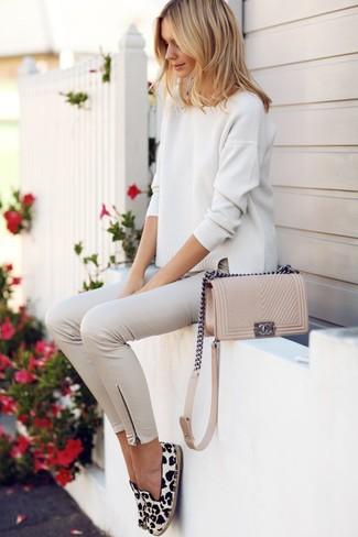 Как и с чем носить: бежевый свободный свитер, бежевые узкие брюки, бело-черные эспадрильи с леопардовым принтом, бежевая кожаная сумка через плечо
