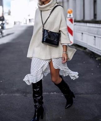 Как и с чем носить: бежевый вязаный свободный свитер, бело-черное платье с запахом в горошек, черные кожаные сапоги, черная кожаная стеганая сумка через плечо