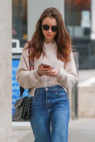 Как и с чем носить: бежевый вязаный свободный свитер, синие джинсы, черная кожаная сумка через плечо с украшением, черные солнцезащитные очки