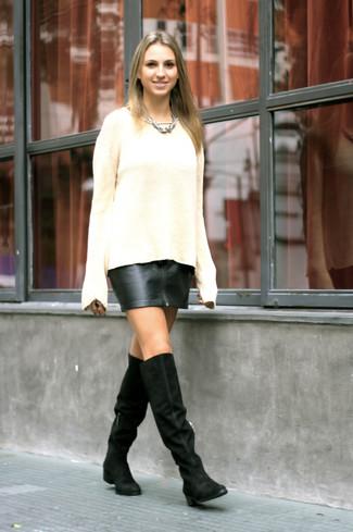 Модный лук: Бежевый вязаный свободный свитер, Черная кожаная мини-юбка, Черные замшевые ботфорты, Серебряное колье