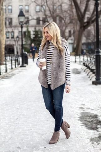 Модные женские луки 2020 фото: Несмотря на то, что это достаточно не сложный ансамбль, тандем серой меховой безрукавки и темно-синих джинсов скинни продолжает завоевывать сердца многих девчонок. В сочетании с этим ансамблем органично выглядят серые замшевые ботильоны.