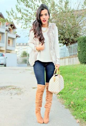 Модный лук: Бежевая меховая безрукавка, Белый свитер с круглым вырезом, Темно-синие джинсы скинни, Светло-коричневые замшевые ботфорты