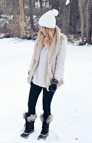 Как и с чем носить: бежевая меховая безрукавка, белый вязаный свободный свитер, черные джинсы скинни, черные зимние ботинки