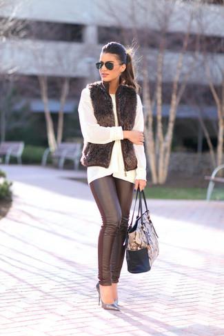 Как и с чем носить: черная меховая безрукавка, белый вязаный свободный свитер, черные кожаные леггинсы, серебряные кожаные туфли