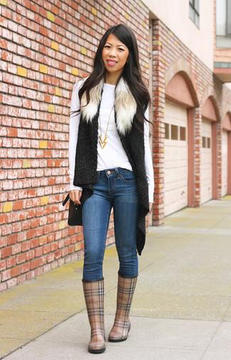 Как и с чем носить: черная меховая вязаная безрукавка, белая футболка с длинным рукавом, синие джинсы скинни, коричневые резиновые сапоги в шотландскую клетку