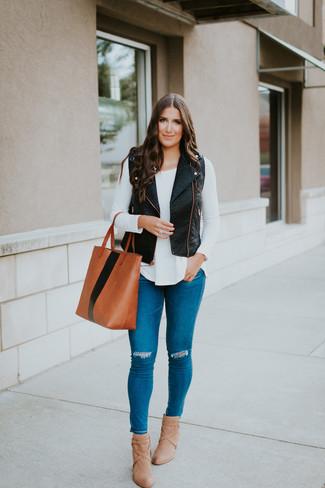 Как и с чем носить: черная кожаная безрукавка, белая футболка с длинным рукавом, синие рваные джинсы скинни, светло-коричневые кожаные ботильоны