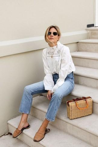 Как и с чем носить: белая блузка с длинным рукавом крючком, голубые джинсы, светло-коричневые замшевые сандалии на плоской подошве, светло-коричневая соломенная большая сумка