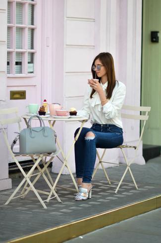 Как и с чем носить: белая шелковая блузка с длинным рукавом, темно-синие рваные джинсы скинни, серебряные кожаные сабо, серая кожаная большая сумка