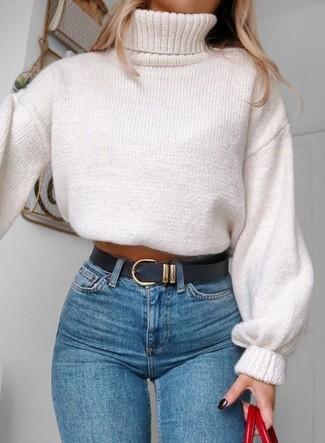 Как и с чем носить: белая вязаная водолазка, синие джинсы скинни, красная кожаная большая сумка, черный кожаный ремень