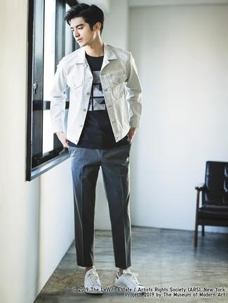 Как и с чем носить: белая джинсовая куртка, черно-белая футболка с круглым вырезом с принтом, темно-серые брюки чинос, белые кожаные низкие кеды
