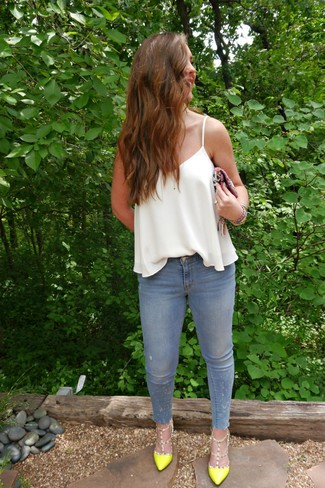 Как и с чем носить: белая шелковая майка, голубые джинсы скинни, зелено-желтые кожаные туфли, разноцветный клатч с вышивкой