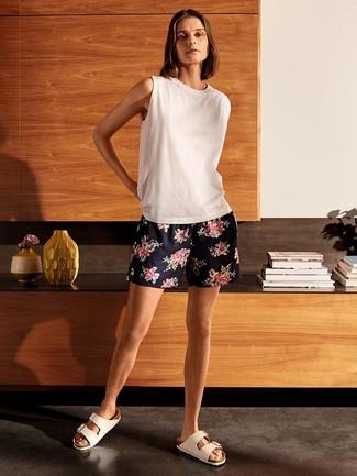 Как и с чем носить: белая майка, темно-синие шорты с цветочным принтом, белые кожаные сандалии на плоской подошве