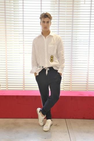 Модный лук: Белая рубашка с длинным рукавом с принтом, Темно-синие брюки чинос, Белые кожаные низкие кеды