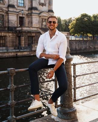 Как и с чем носить: белая рубашка с длинным рукавом, темно-синие брюки чинос в вертикальную полоску, белые кожаные низкие кеды, коричневые солнцезащитные очки