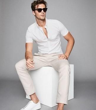С чем носить белые кожаные низкие кеды мужчине: Сочетание белой рубашки с коротким рукавом и бежевых брюк чинос — отличный вариант для создания мужского ансамбля в стиле smart casual. Белые кожаные низкие кеды — отличный вариант, чтобы закончить образ.