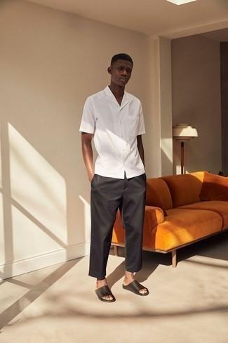 Белая рубашка с коротким рукавом в вертикальную полоску: с чем носить и как сочетать мужчине: Белая рубашка с коротким рукавом в вертикальную полоску в сочетании с черными брюками чинос позволит выразить твою индивидуальность. Такой лук несложно адаптировать к повседневным делам, если надеть в тандеме с ним черные кожаные сандалии.