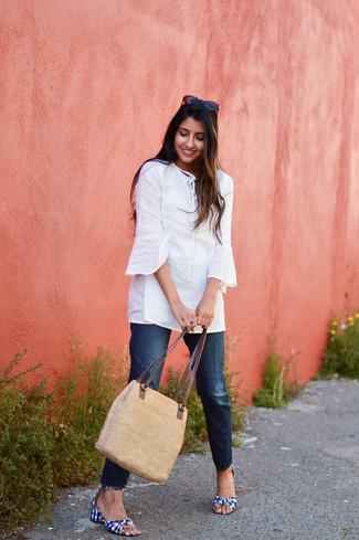 Как и с чем носить: белая туника, темно-синие джинсы, темно-сине-белые босоножки на каблуке из плотной ткани в мелкую клетку, светло-коричневая соломенная большая сумка