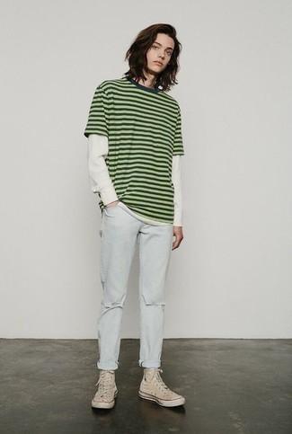 Мода для подростков парней: Зелено-желтая футболка с круглым вырезом в горизонтальную полоску и голубые рваные джинсы — стильный выбор молодых людей, которые никогда не сидят на месте. Переходя к обуви, можно завершить ансамбль бежевыми высокими кедами из плотной ткани.