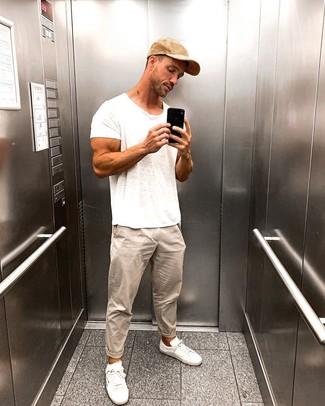 Как и с чем носить: белая футболка с круглым вырезом, бежевые брюки чинос, белые низкие кеды, светло-коричневая бейсболка