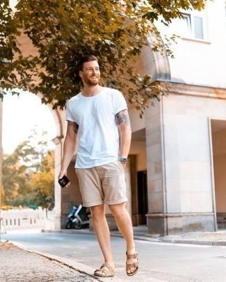 Модные мужские луки 2020 фото в спортивном стиле: Несмотря на свою несложность, тандем белой футболки с круглым вырезом и бежевых шорт приходится по душе стильным мужчинам, покоряя при этом сердца девушек. Создать интересный контраст с остальными элементами этого образа помогут светло-коричневые замшевые сандалии.