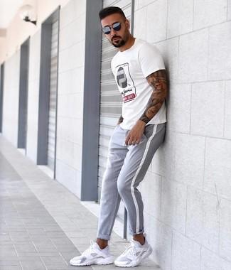 Как и с чем носить: белая футболка с круглым вырезом с принтом, серые брюки чинос, белые кроссовки, темно-синие солнцезащитные очки