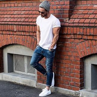 Белую футболку с круглым вырезом и синие зауженные джинсы можно надеть на вечернюю прогулку с девушкой или для барного тура с друзьями. Если ты предпочитаешь смелые решения в своих образах, дополни этот белыми низкими кедами.