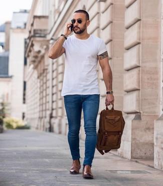 Как и с чем носить: белая футболка с круглым вырезом, синие зауженные джинсы, коричневые кожаные ботинки челси, коричневый рюкзак