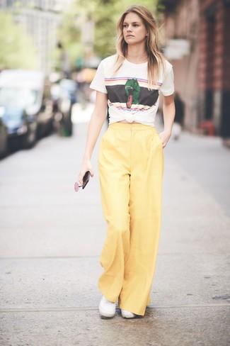 Как и с чем носить: белая футболка с круглым вырезом с принтом, желтые широкие брюки, белые низкие кеды из плотной ткани