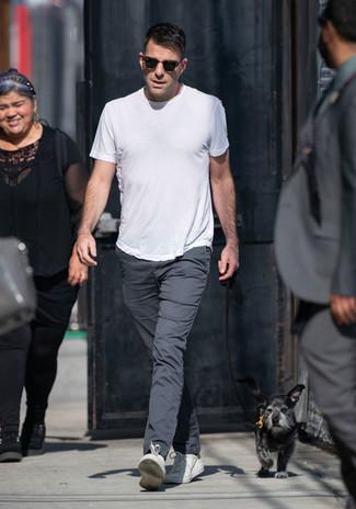 Как и с чем носить: белая футболка с круглым вырезом, темно-серые брюки чинос, белые кожаные низкие кеды, темно-коричневые солнцезащитные очки