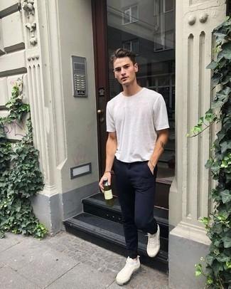 Модный лук: белая футболка с круглым вырезом, темно-синие брюки чинос, белые кроссовки