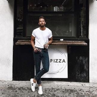 Модные мужские луки 2020 фото: Тандем белой футболки с круглым вырезом и темно-синих джинсов поможет выглядеть аккуратно, но при этом выразить твой личный стиль. Весьма уместно здесь выглядят бело-черные низкие кеды из плотной ткани.