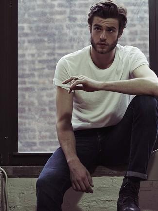 Белая футболка с круглым вырезом стильно сочетается с темно-синими джинсами. Если ты не боишься смешивать разные стили, на ноги можно надеть черные кожаные ботинки.