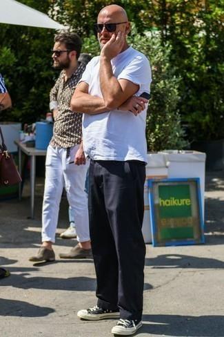 Модные мужские луки 2020 фото в жару: Белая футболка с круглым вырезом и черные брюки чинос будет превосходным вариантом для простого повседневного образа. Весьма уместно здесь будут выглядеть черно-белые низкие кеды из плотной ткани.