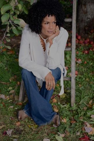Как и с чем носить: белая шелковая блузка с длинным рукавом, синие джинсы-клеш, коричневые кожаные ботильоны
