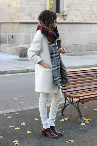 Как и с чем носить: белое пальто, белые джинсы скинни, темно-красные кожаные ботильоны, серый шарф в шотландскую клетку