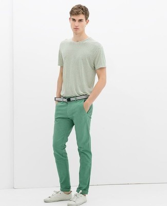 Модные мужские луки 2020 фото: Образ из бело-зеленой футболки с круглым вырезом в горизонтальную полоску и зеленых брюк чинос выглядит привлекательно и современно. Вместе с этим ансамблем органично выглядят белые низкие кеды из плотной ткани.