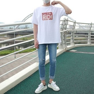 Как и с чем носить: бело-красная футболка с круглым вырезом с принтом, синие рваные зауженные джинсы, белые кожаные низкие кеды