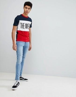 Как и с чем носить: бело-красно-синяя футболка с круглым вырезом с принтом, голубые зауженные джинсы, черно-белые низкие кеды из плотной ткани, белые носки