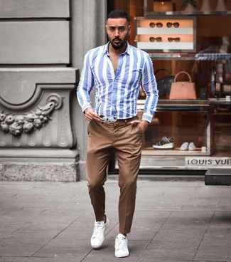 Как и с чем носить: бело-синяя рубашка с длинным рукавом в вертикальную полоску, коричневые брюки чинос, белые кожаные низкие кеды, коричневые солнцезащитные очки