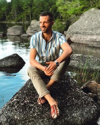 Как и с чем носить: бело-синяя рубашка с коротким рукавом в вертикальную полоску, оливковые зауженные джинсы, разноцветные слипоны из плотной ткани с принтом, серебряные часы